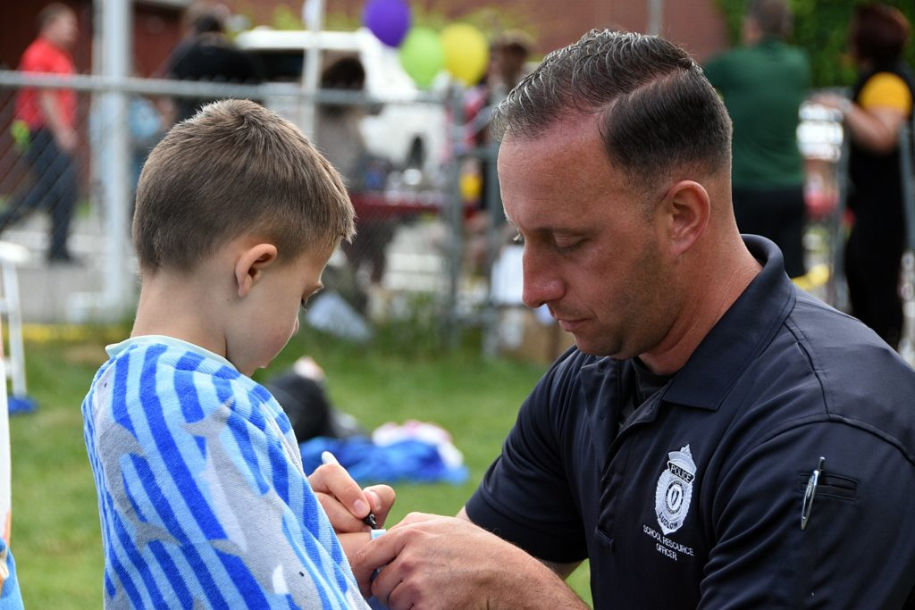 Ludlow Police officer marking a child's bracelet